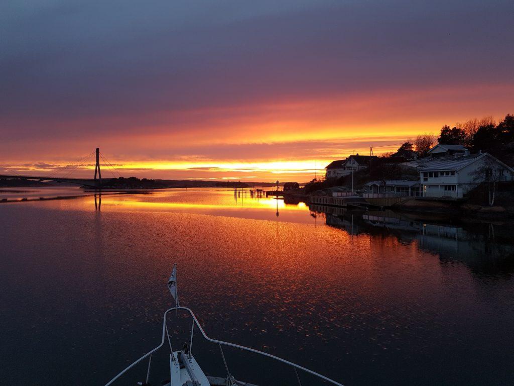 En vakker høstkveld med varmt lys . Det er gule, røde og rosa skyer som reflekteres i sjøen. Bildet er tatt fra flybrigde på M/Y Solbris