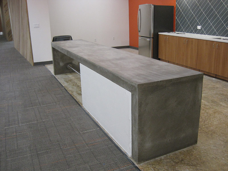 other side of cement table with waterfall edge around a white cabinet