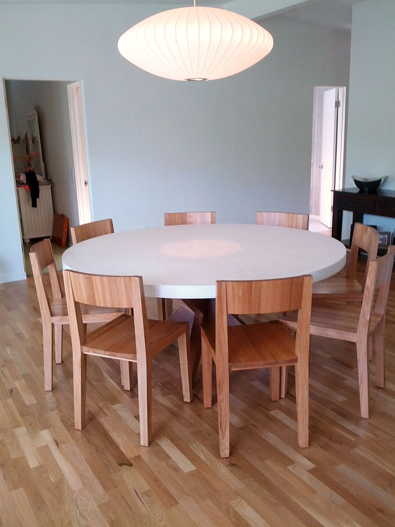 white round concrete table in living room with chairs