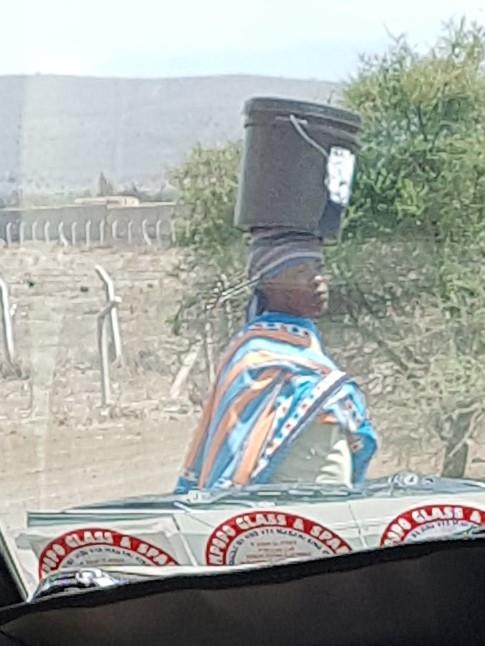 Maasai woman carrying bucket on head