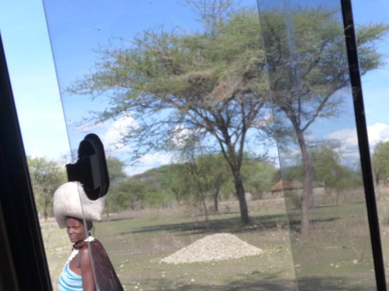 Maasai woman carrying sack on head