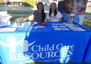 Two women smile at Child Care Resources table