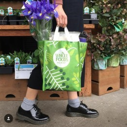 Person walking with a Whole Foods Market shopping bag with purple lilies in it