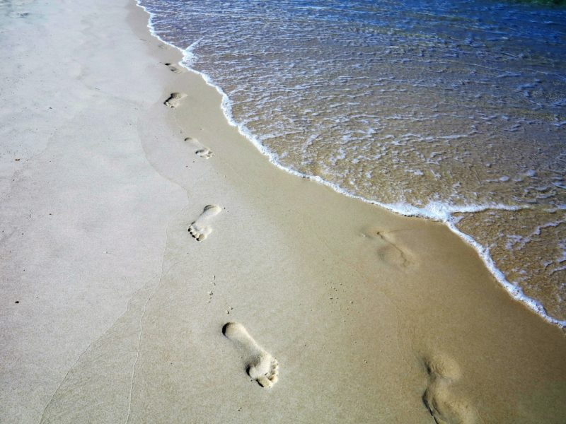 Image is of geraldinemoreno via Twenty20 and shows footprints on the beach with seawater