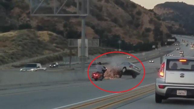 Motociclista patea un auto y lo manda a volar