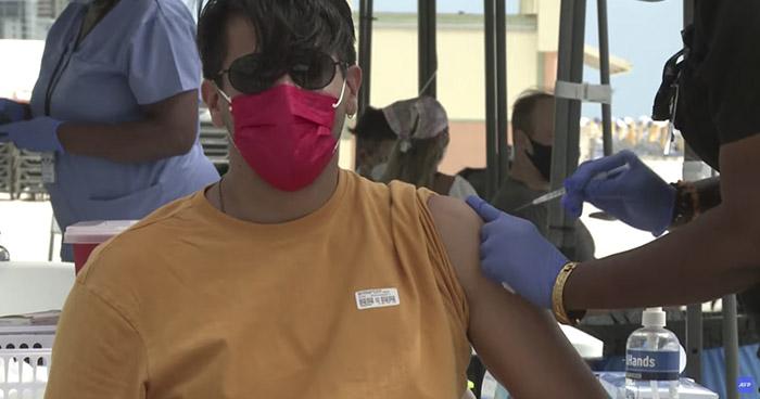 Turistas latinos se vacunan contra el COVID-19 en playa de Miami Beach