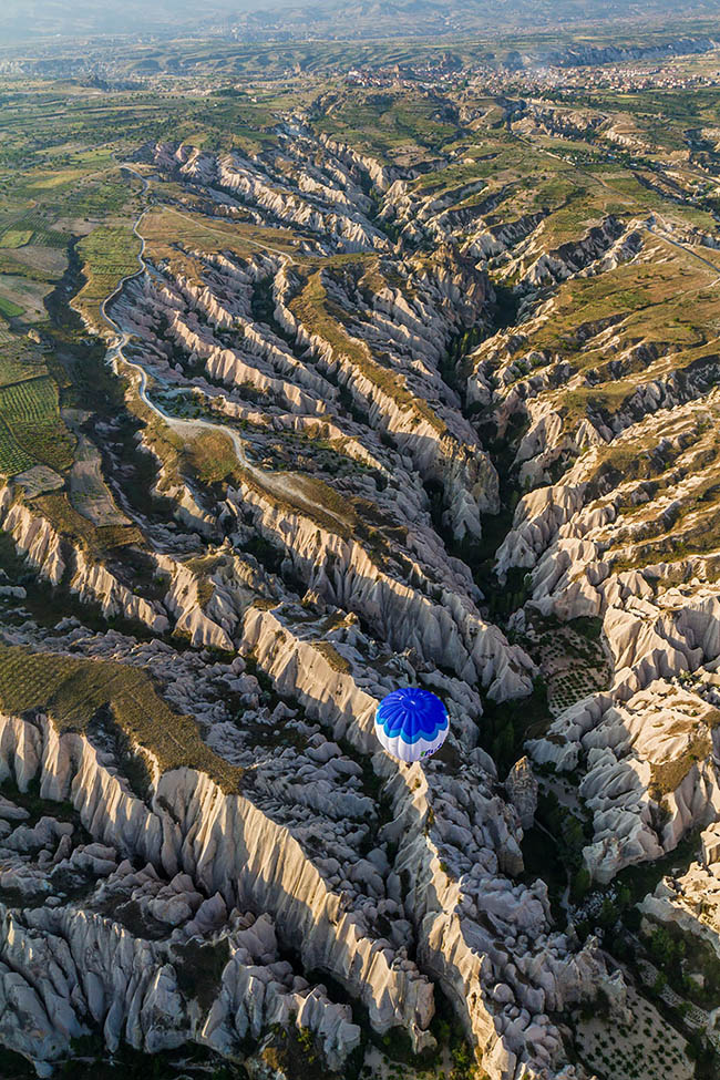 Sharp, jaggered landscape photograph of a Turkish valley and a hot air balloon