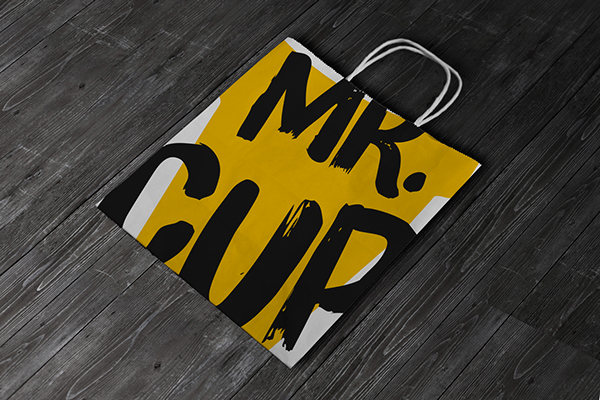 MR. CUP paper bag - branding has a massive 'MR. CUP' written on the bag in black with yellow and white background