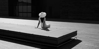 Light and shadow, black and white photograph showing a woman perched on a rectangular shaped , long bench with her back facing us. She is wearing a white hate and white t-shirt and trousers, looking at a dark, block building . The floor is made of wood.