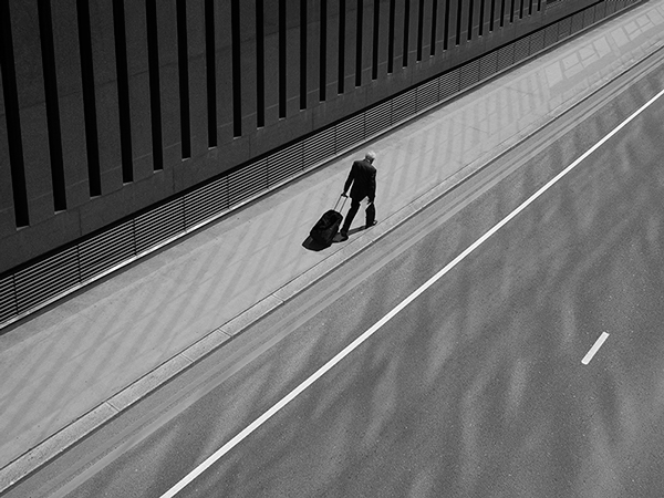 Black and white photograph taken overhead and looking down on the subject. Subject is wearing a black suit, trailing behind him a black suitcase / work bag. He is walking along a silvery path next to a road where the building's windows from next to him is reflecting on the road.
