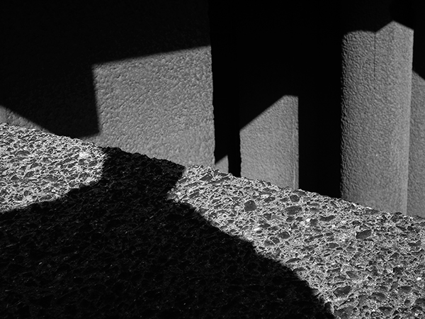 Photograph taken with a textured concrete block looking downwards onto concrete polls