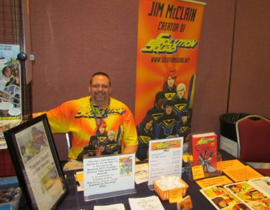 Jim McClain at a Solution Squad comic con table. There is a Solution Squad banner and Solution Squad materials and books on display.