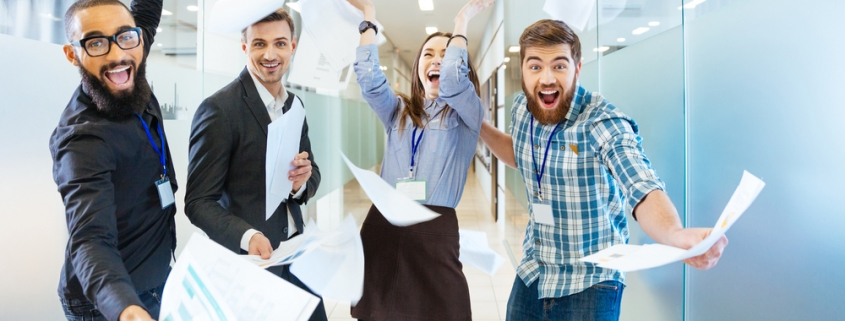 Group-of-joyful-excited-business-people-throwing-papers-and-having-fun-in-office