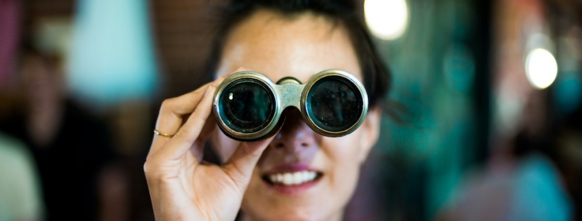 Blog header image showing a woman with binoculars for the Solver blog on how to use monthly rolling forecasts to gain insight in unpredictable times