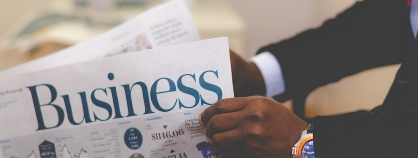 Blog header image of a businessman reading the business news for 13 recommended CPM software tools for effective KPI management blog from Solver