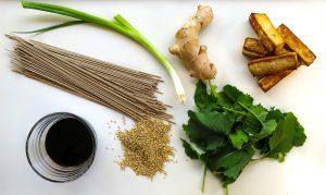 Soba noodles, tofu, sesame seeds, greens, soy sauce, and ginger