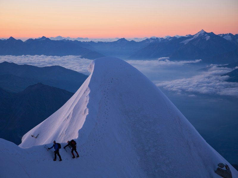 Rob Jarvis and client at day break in a horizontal climb over a snow peak.