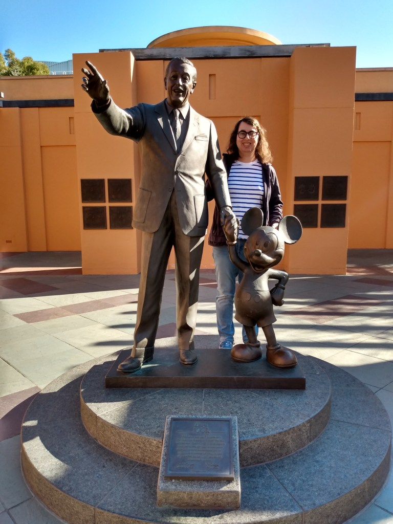 Danielle Solzman poses with statues of Walt Disney and Mickey Mouse.