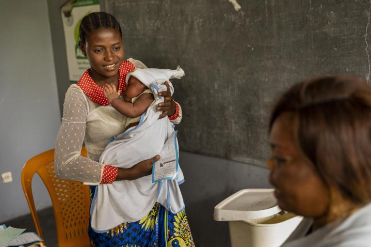 On 27 January 2020, Mama Bwanga, 25, holds her son, Dieu Merci, 1 month, as they wait to be seen at a health clinic in Nsele district, Democratic Republic of the Congo (DRC). Bwanga's two youngest children, sons Dieu Merci and Mélé, 7, will receive measles vaccines; daughter Raissa, 10, has already been vaccinated.