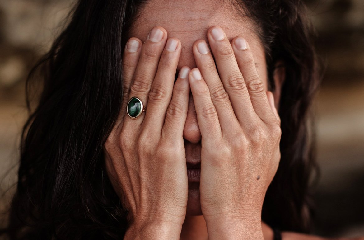 Woman covering her face, overcoming shame