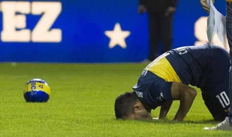 Boca Juniors' newly returned player Carlos Tevez kisses the field during his official presentation at La Bombonera stadium in Buenos Aires, on July 13, 2015. AFP PHOTO / ALEJANDRO PAGNI (Photo credit should read ALEJANDRO PAGNI/AFP/Getty Images)