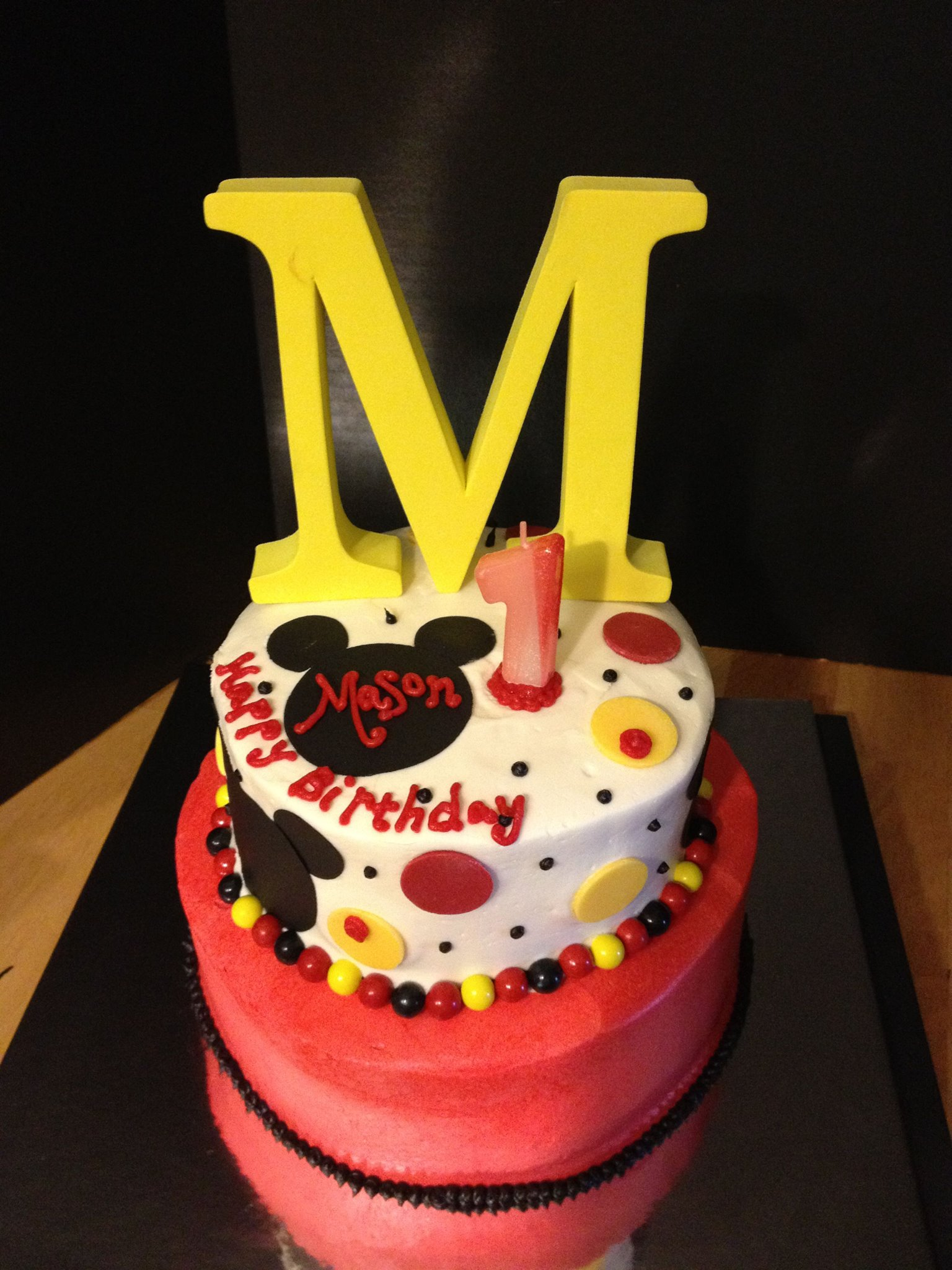 Disney Mickey Mouse Themed Cake with fondant and sugar sheet decor topped with a foam M