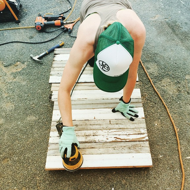 When we think sand and sun, this is what we mean! Tiffany giving a little sandin' to the side panel of our in progress reclaimed wood bar made from 100 year old beadboard from a row house in Columbia Heights.  #reclaimed #salvage #create #build #girlboss #vintage #aCreativeDC #dc #columbiaheights #welovedc #green