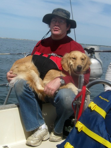 Honey the Golden Retriever tries to nap in the sailboat cockpit.
