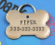 Hand stamped bronze dog tag from Etsy.