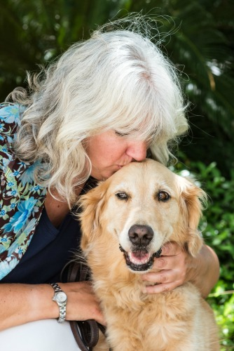 Pam kisses Honey the golden retriever on the head in a professional photograph.