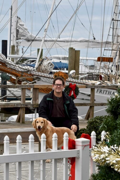 Learn about the wrong way to train your dog with treats. (Honey the golden retriever waits with Mike in front of a boat.)