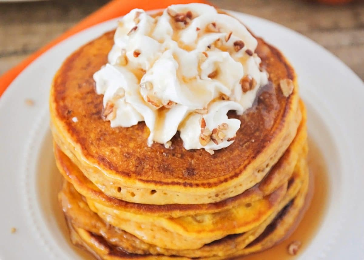 Stack of 3 orange pumpkin pancakes made using the best Pumpkin Pancake Recipe you will find. The pancakes are topped with syrup, whipped cream and nuts on a white plate.