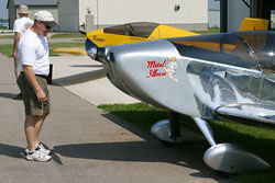 """A Fly-In attendee inspects Kerry Fores' """"Metal Illness""""."""