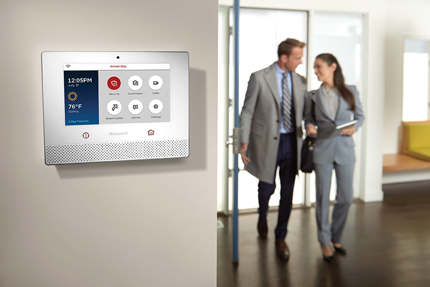 Image of Couple Walking into Home with Alarm Control Panel in Forefront – Lifestyle; Honeywell Lyric™ in Vancouver & Toronto Canada