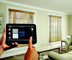 Person Controlling Motorized Blinds with Black Tablet Device Controller. Available from Crestron, Fibaro & Atlona at Sonic Systems Toronto & Vancouver Stores