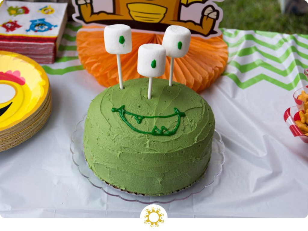 Green monster birthday cake with marshmallow eyes on a decorated table (with logo overlay)