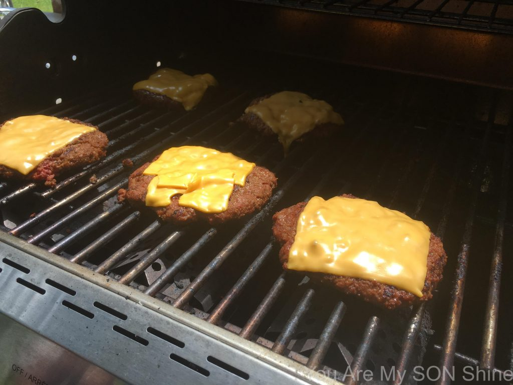 BBQ burgers topped with slices of cheese on the grill
