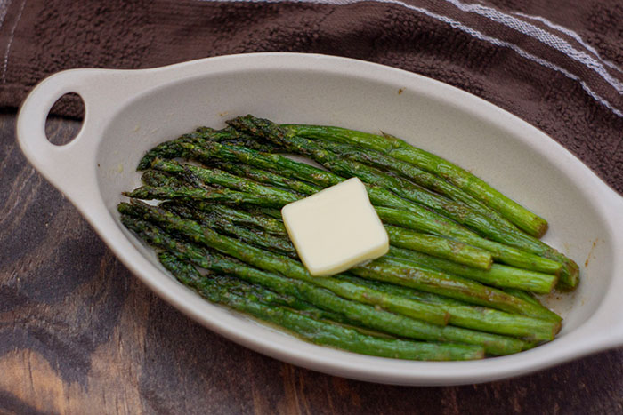Roasted Asparagus in an oval bowl with a pat of butter on top