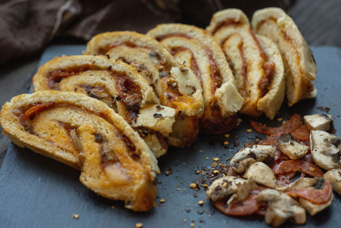 Sliced stromboli next to a pile of pepperoni, mushrooms, and red pepper flakes on a slate serving platter in front of a brown towel