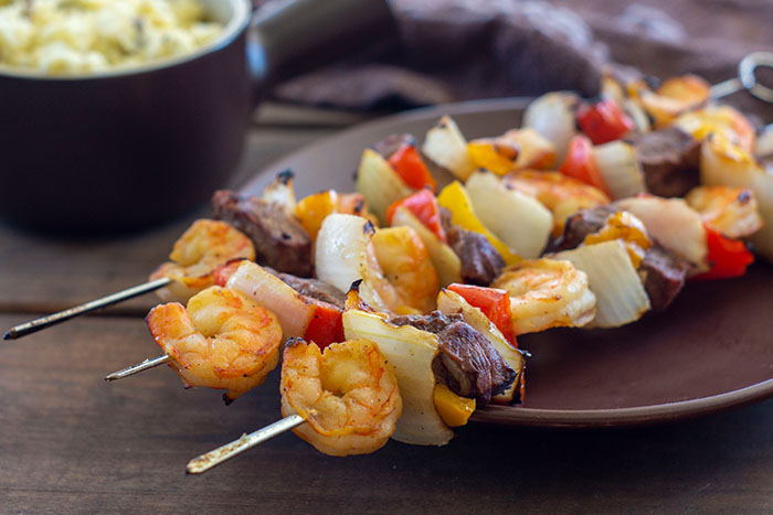 Steak and Shrimp Kabobs on a brown plate with a bowl of potato salad in the background