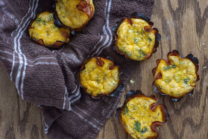 Overhead view of baked ham, egg, and cheese quiche cups sitting on a brown towel and on a wooden surface