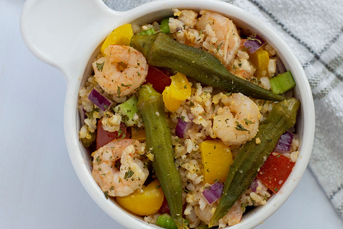 Shrimp and okra bowl recipe in a white bowl with a towel next to it
