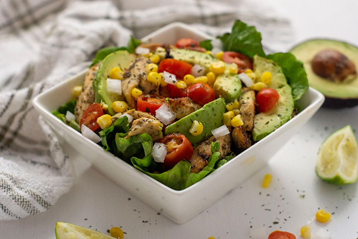 Easy Tex-Mex Bowl in a square white bowl with ingredients around the bowl and a towel in the background