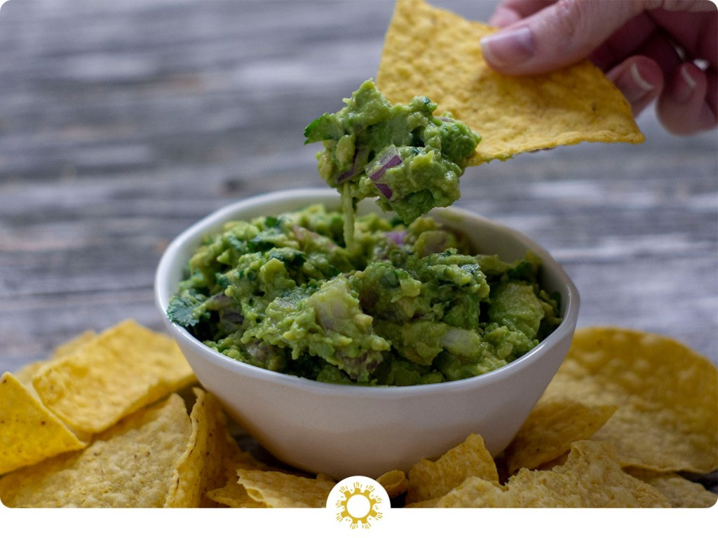 Woman's hand pulling a tortilla chip from a white bowl of guacamole surrounded by tortilla chips on a wooden surface (with logo overlay)