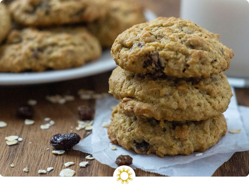 Three oatmeal raisin cookies stacked on pieces of parchment paper with oats and raisins around them with a plate of cookies and a glass of milk behind all on a wooden surface (with logo overlay)