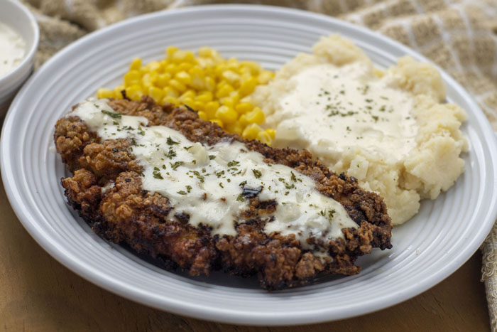 Creamy Buttermilk Chicken-Fried Chicken covered with white gravy next to mashed potatoes with gravy and steamed corn on a round white plate