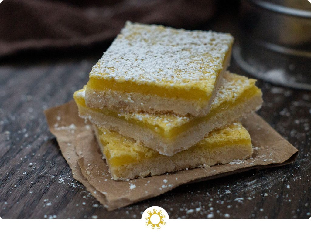Three lemon bars stacked on top of each other sprinkled with powdered sugar sitting on a piece of brown paper on a wooden surface (with logo overlay)