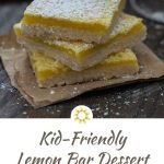 Three lemon bars stacked on top of each other sprinkled with powdered sugar sitting on a piece of brown paper on a wooden surface (with title overlay)