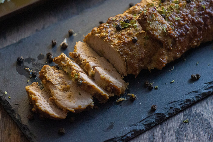 Marinated Baked Pork on a dark granite platter on a wooden surface