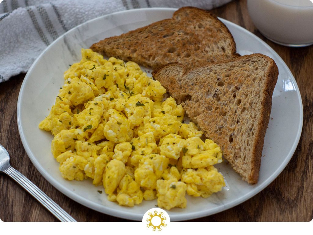 Fluffy and Yummy Scrambled Eggs on a round white plate with two slices of triangle-cut toast next to a fork, a glass of milk, and a white and grey towel all on a wooden surface (with logo overlay)